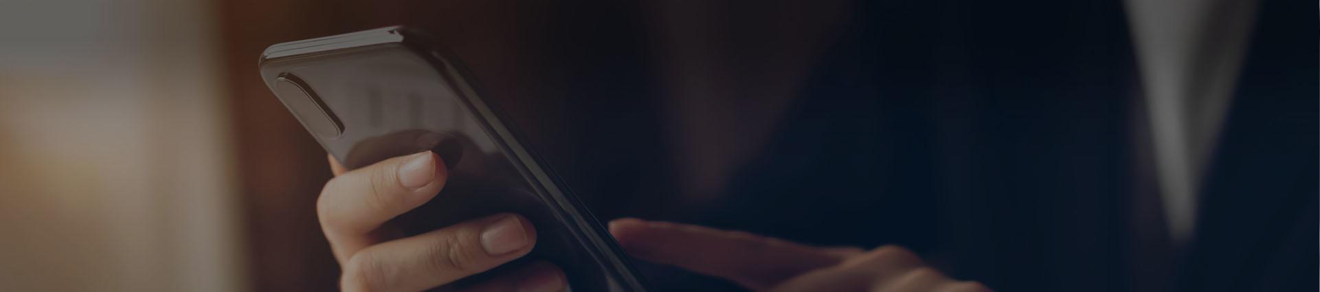 osoba trzyma w dłoni telefon komórkowy